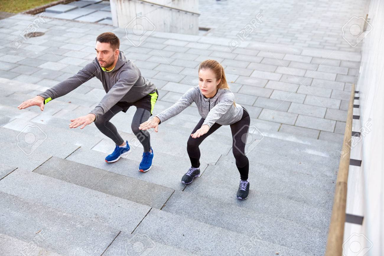 fitness, sport, people, exercising and lifestyle concept - couple doing squats on city street stairs - 62566008