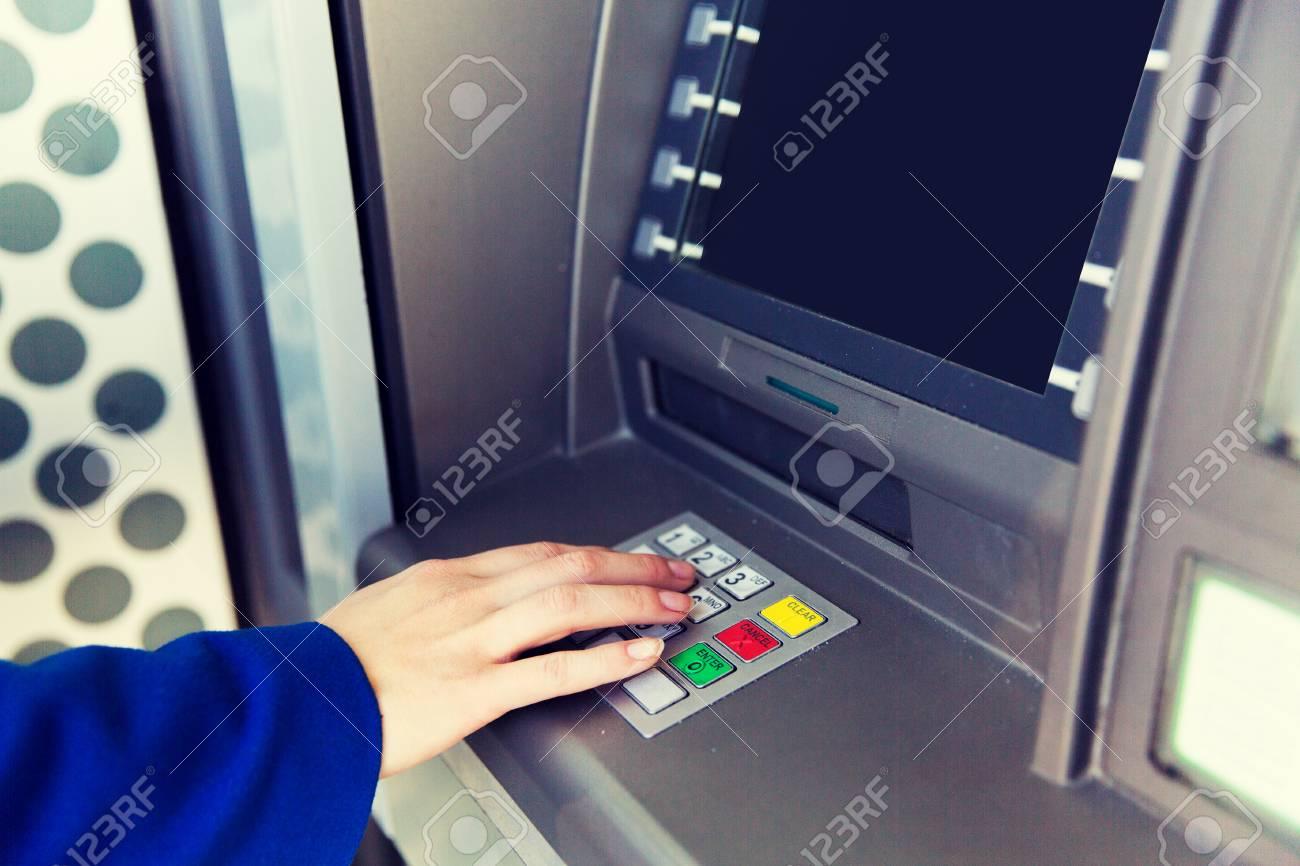 Concepto de finanzas, tecnología, dinero y personas cerca de la mano que ingresa el código PIN en el cajero automático