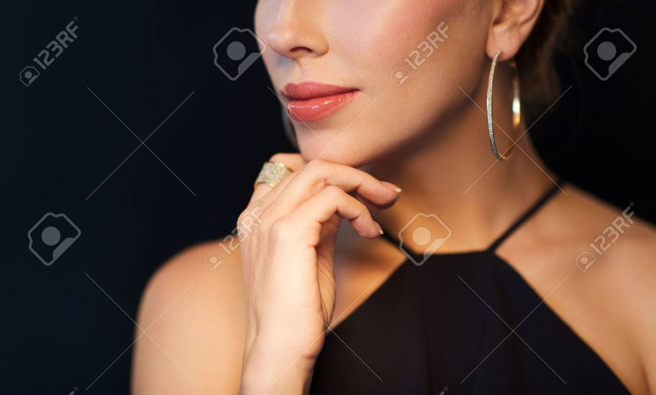 people, luxury, jewelry and fashion concept - beautiful woman in black wearing diamond earring and ring over dark background - 63062871