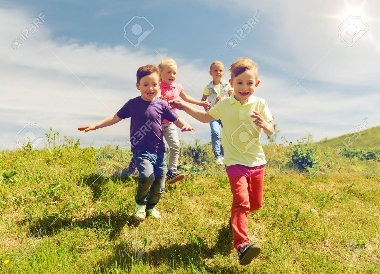 summer, childhood, leisure and people concept - group of happy kids playing tag game and running on green field outdoors - 63064321