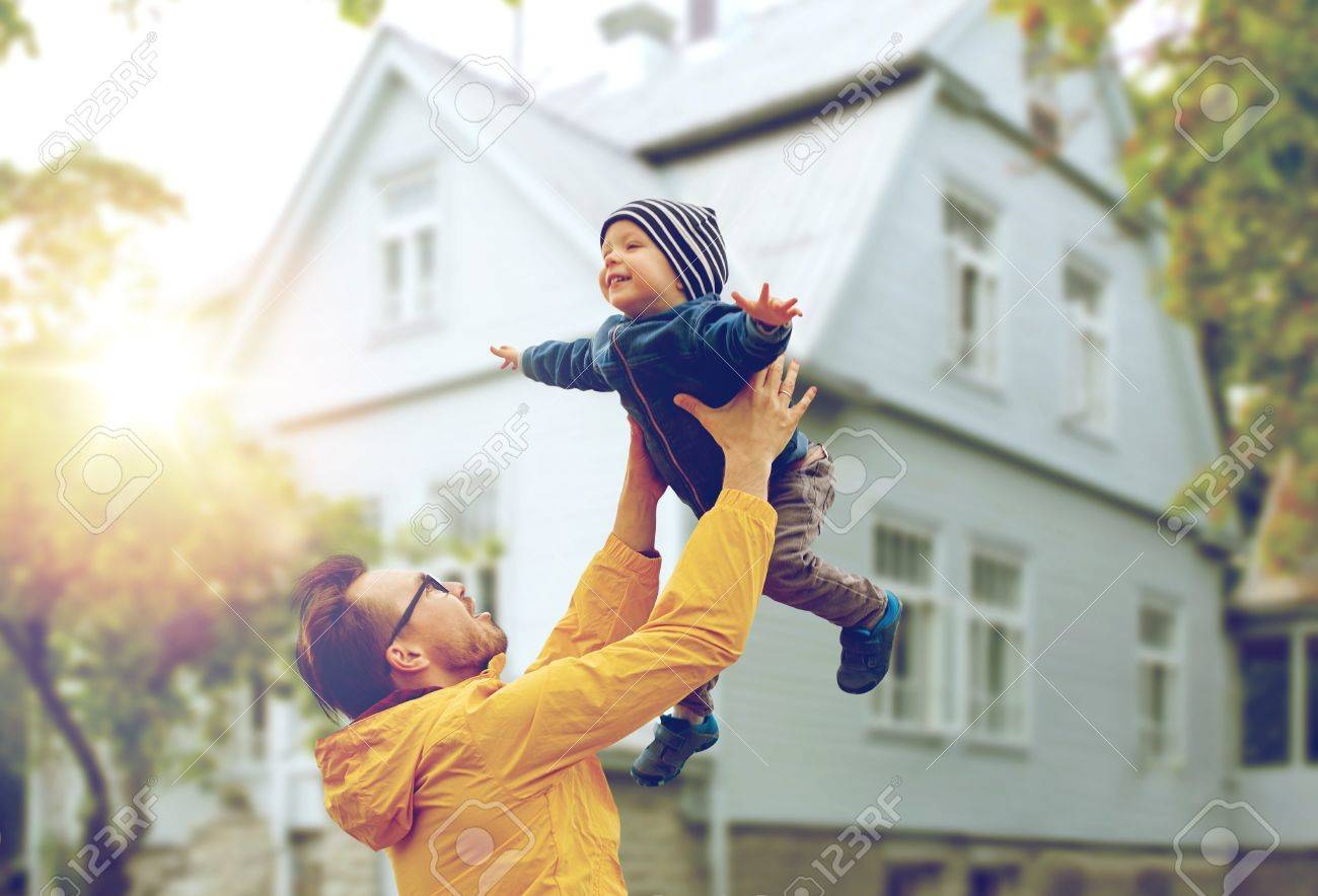 family, childhood, fatherhood, leisure and people concept - happy father and little son playing and having fun outdoors over living house background - 63161309