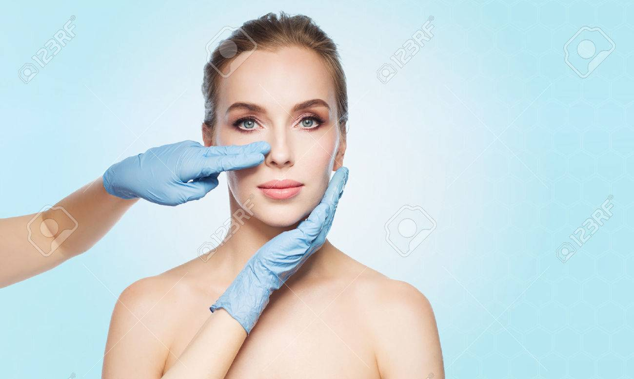 people, cosmetology, plastic surgery and beauty concept - surgeon or beautician hands touching woman face over blue background Banque d'images - 63325205