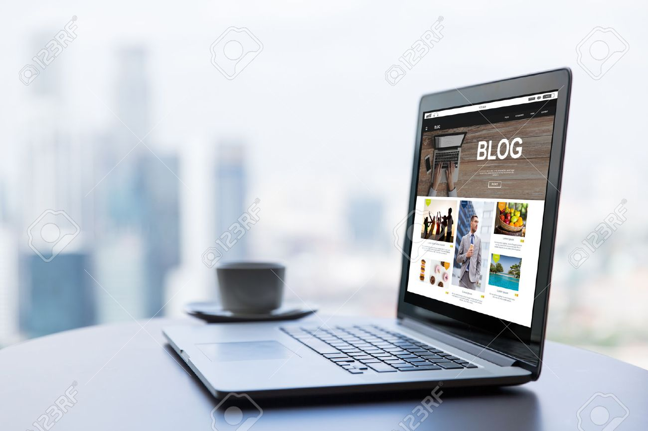 technology, business, mass media, internet and modern life concept- close up of open laptop computer with blog web page on screen and coffee cup on table at office or hotel room Banque d'images - 63415644