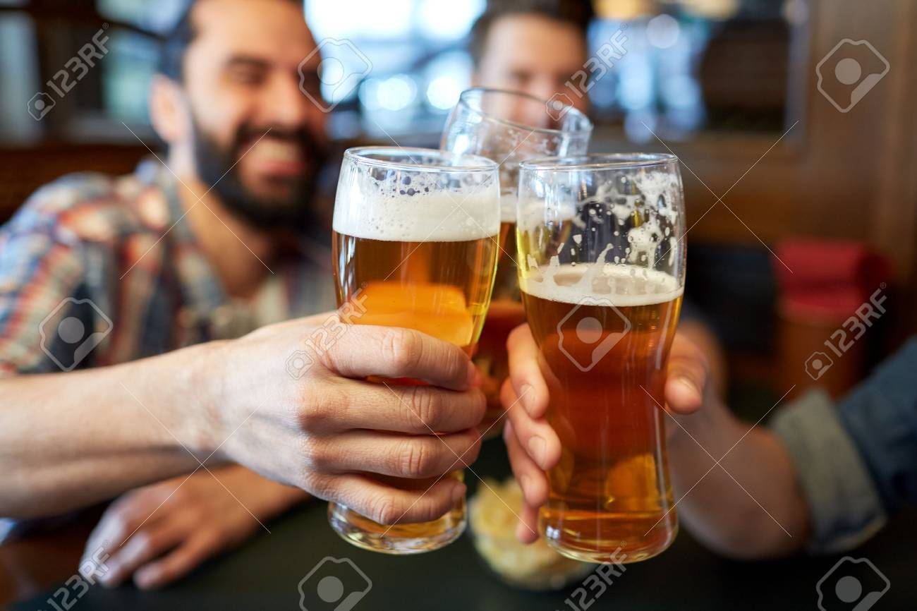 people, men, leisure, friendship and celebration concept - happy male friends drinking beer and clinking glasses at bar or pub Standard-Bild - 64425819
