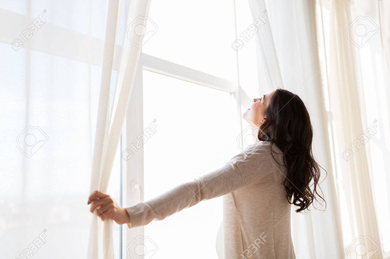 pregnancy, motherhood, people and expectation concept - close up of happy pregnant woman opening window curtains Banque d'images - 63688392