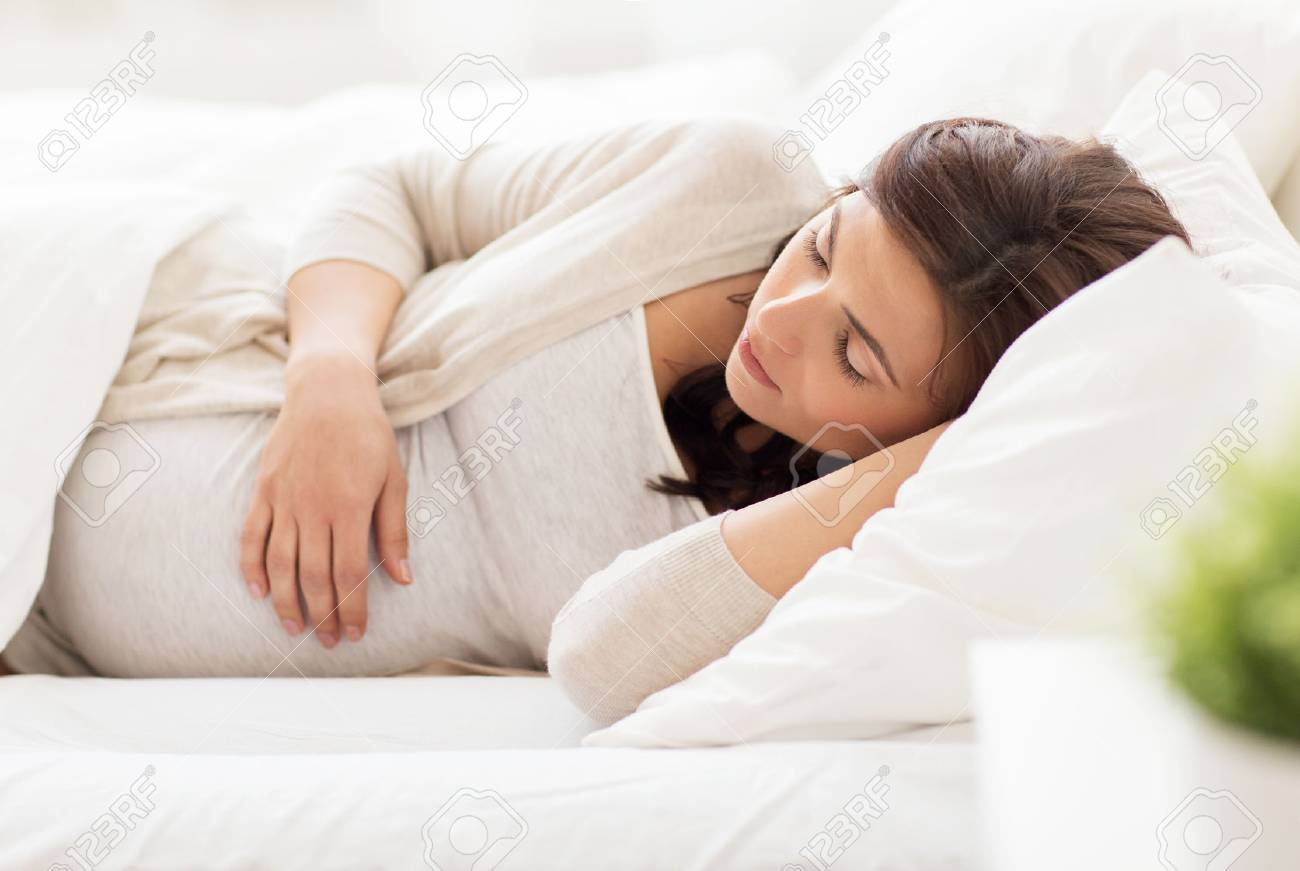 pregnancy, rest, people and expectation concept - happy pregnant woman sleeping in bed at home Banque d'images - 63832306