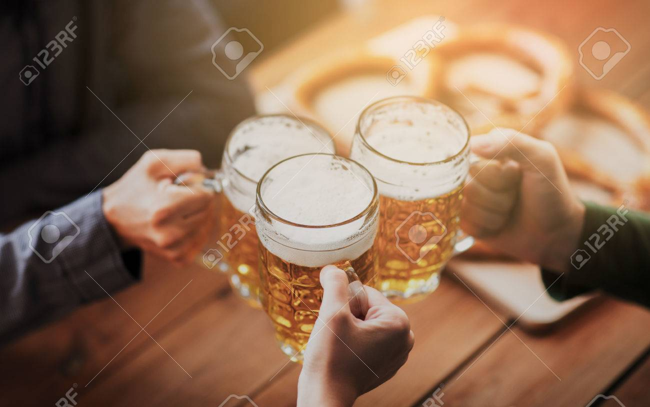 people, leisure and drinks concept - close up of hands clinking beer mugs at bar or pub Standard-Bild - 63832419