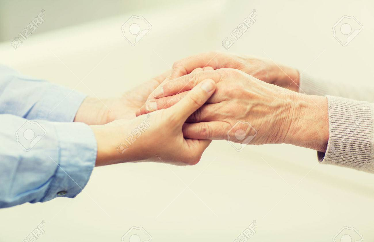 people, age, family, care and support concept - close up of senior and young woman  holding hands Standard-Bild - 63833231