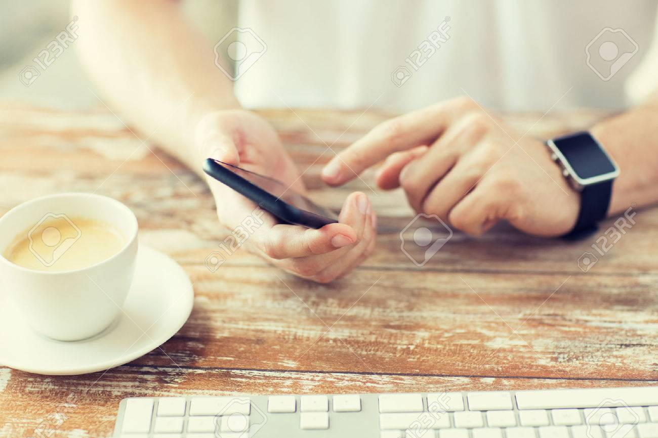 business, technology and people concept - close up of male hand holding smart phone and wearing watch with coffee and keyboard at wooden table Standard-Bild - 64173039