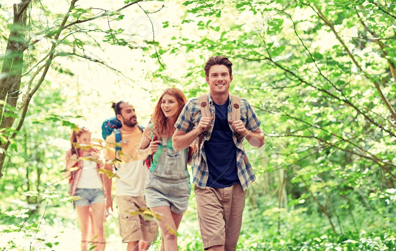 adventure, travel, tourism, hike and people concept - group of smiling friends walking with backpacks in woods Banque d'images - 64214508