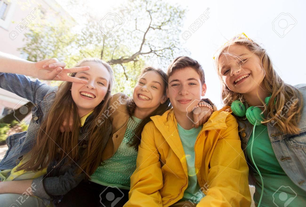 Konzept Freundschaft und die Menschen - glücklich Teenager Freunden oder High-School-Studenten, die Spaß haben und machen Gesichter Standard-Bild - 64298094