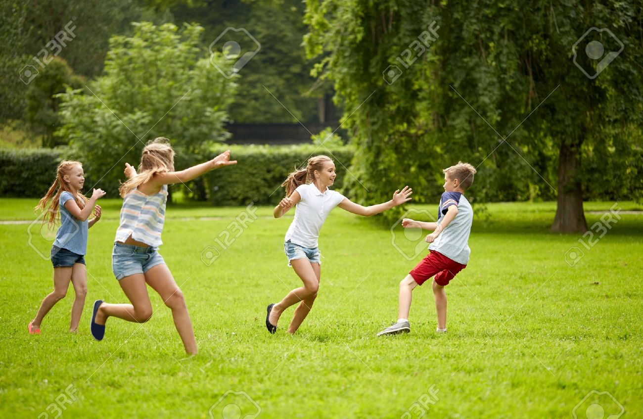 friendship, childhood, leisure and people concept - group of happy kids or friends playing catch-up game and running in summer park Standard-Bild - 65048500