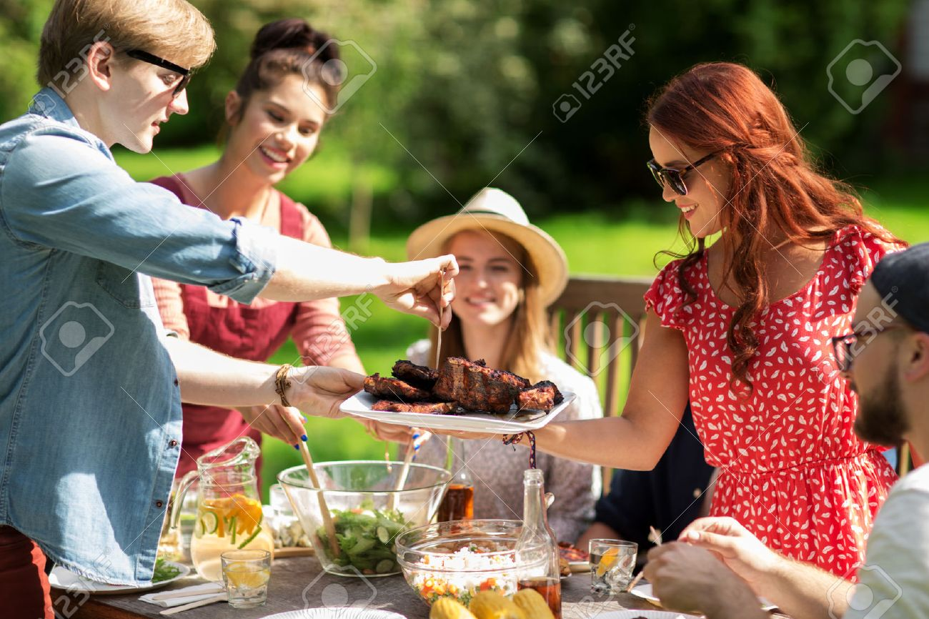 leisure, holidays, eating, people and food concept - happy friends having meat for dinner at summer garden party Standard-Bild - 64662990