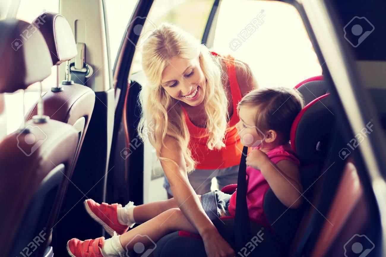 Familie, Verkehr, Sicherheit, Straße Reise und Personen Konzept - glückliche Mutter Befestigungs Kind mit Autogurt Standard-Bild - 64663537
