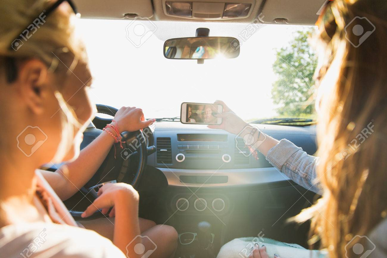 summer vacation, holidays, travel, road trip and people concept - happy teenage girls or young women with smartphone taking selfie in car Standard-Bild - 64639495