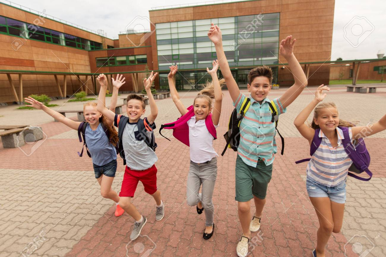 primary education, friendship, childhood and people concept - group of happy elementary school students with backpacks running and waving hands outdoors - 64634378