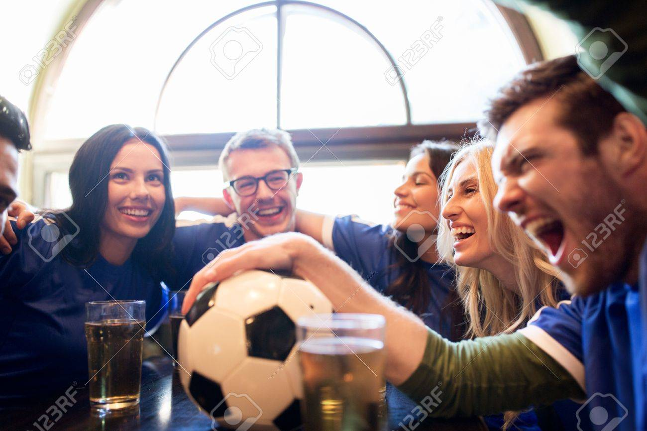 sport, people, leisure, friendship and entertainment concept - happy football fans or friends drinking beer and celebrating victory at bar or pub Standard-Bild - 64635626