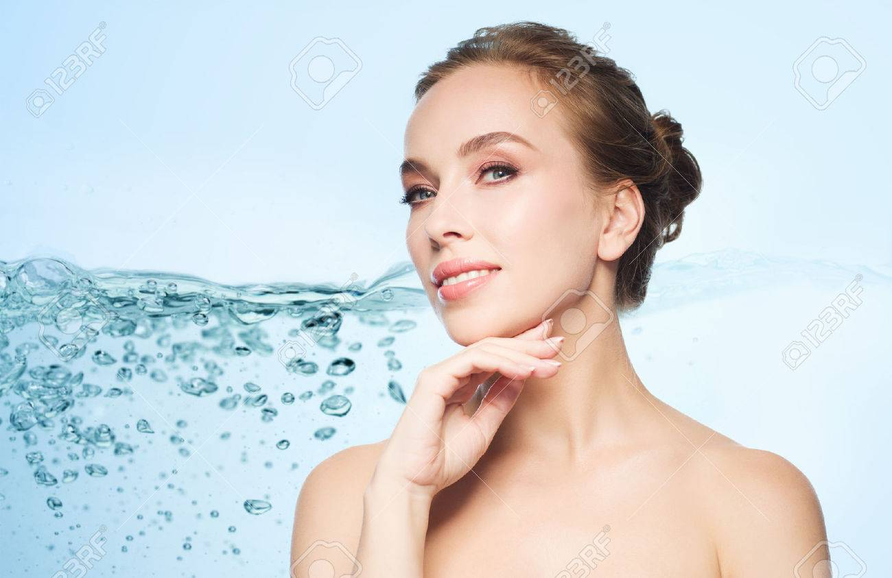 beauty, people and health concept - beautiful young woman touching her face over blue background with water splash Standard-Bild - 64677035