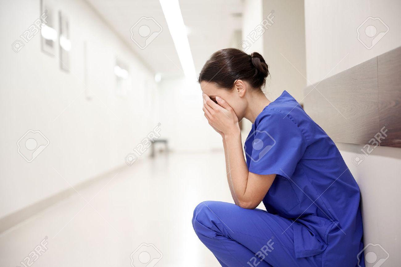 Menschen, Medizin, Gesundheitswesen und Trauer Konzept - traurig oder weibliche Krankenschwester im Krankenhaus Korridor weinen Standard-Bild - 64678364