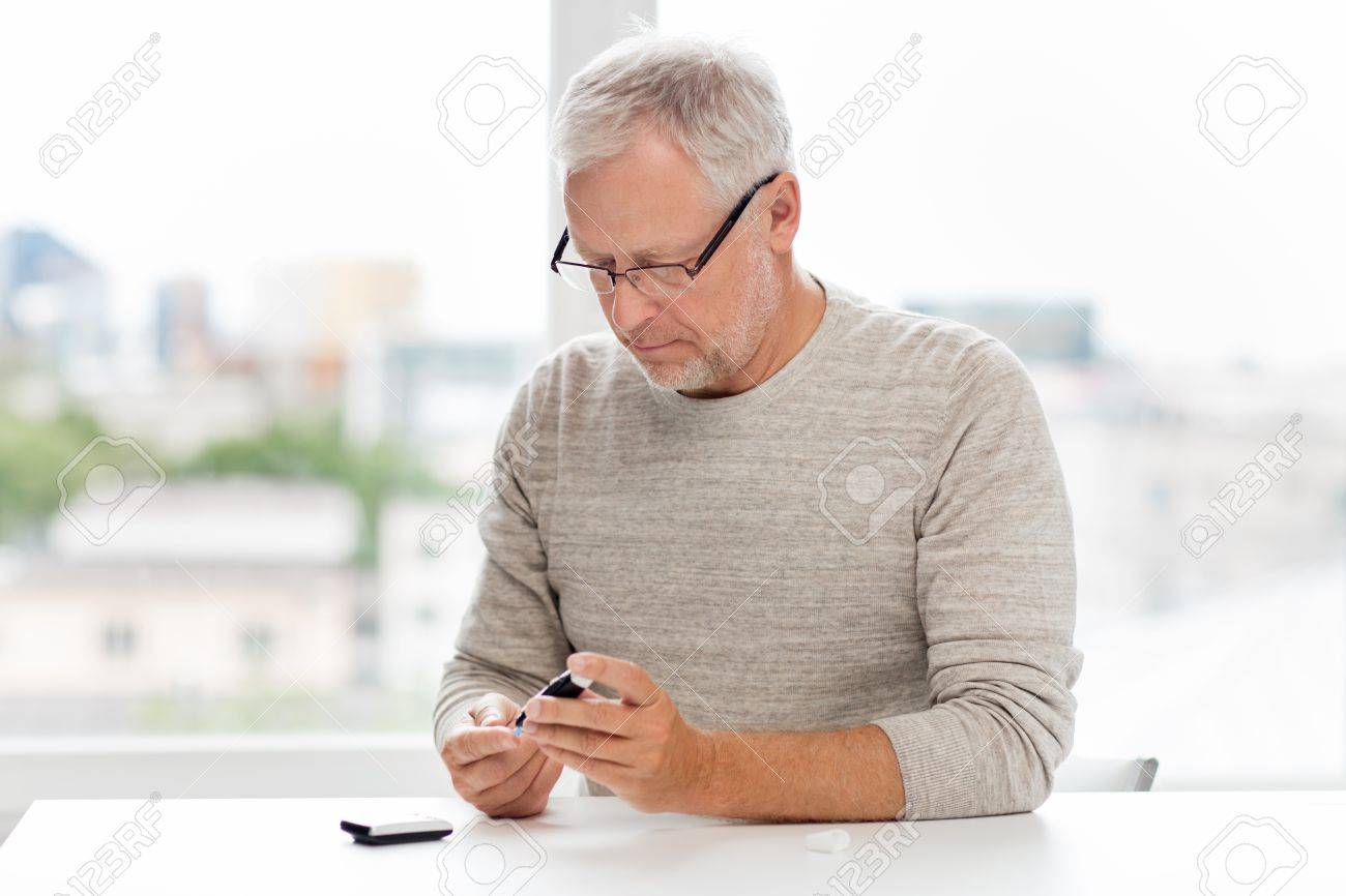 medicine, age, diabetes, health care and old people concept - senior man with glucometer checking blood sugar level at home - 64682653