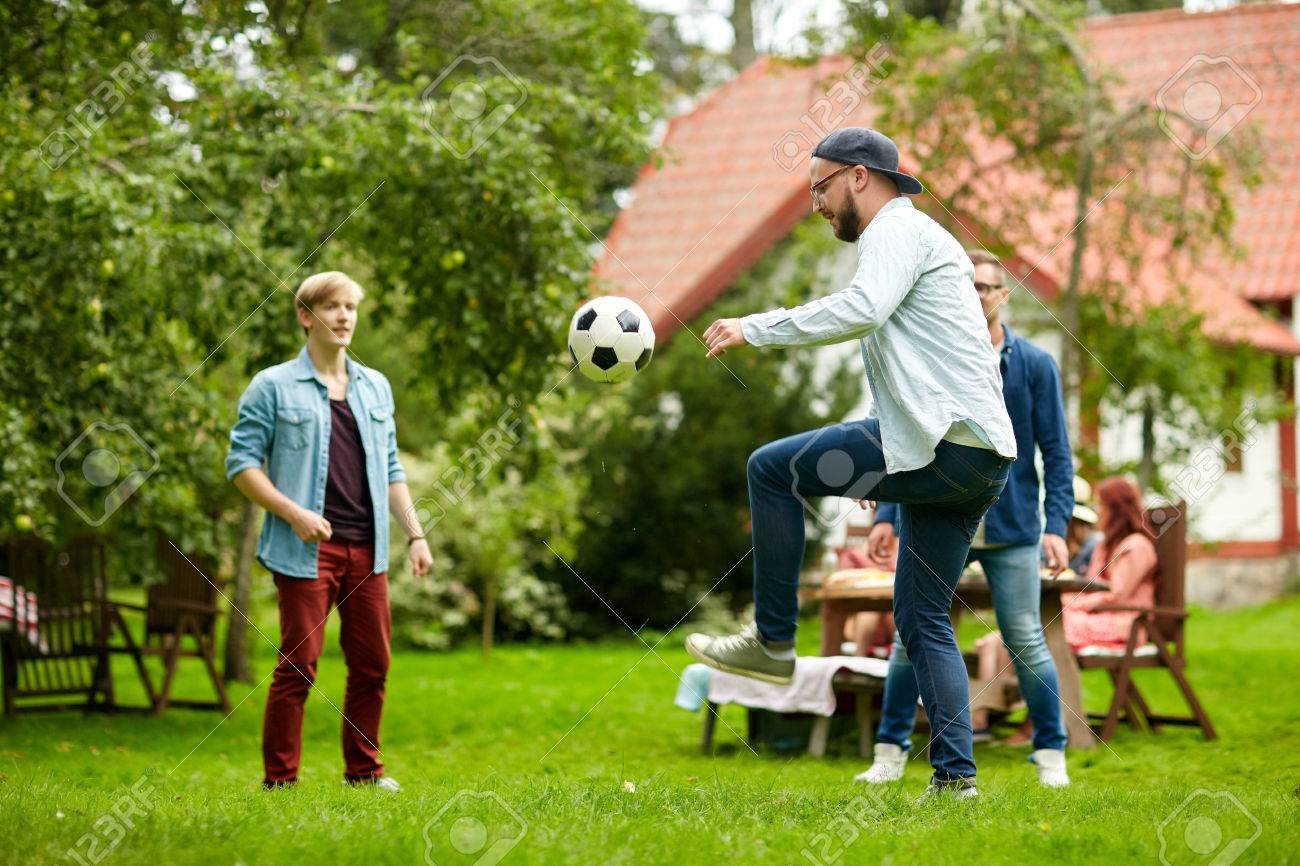 leisure, holidays, people and sport concept - happy friends playing football at summer garden party Standard-Bild - 65132159