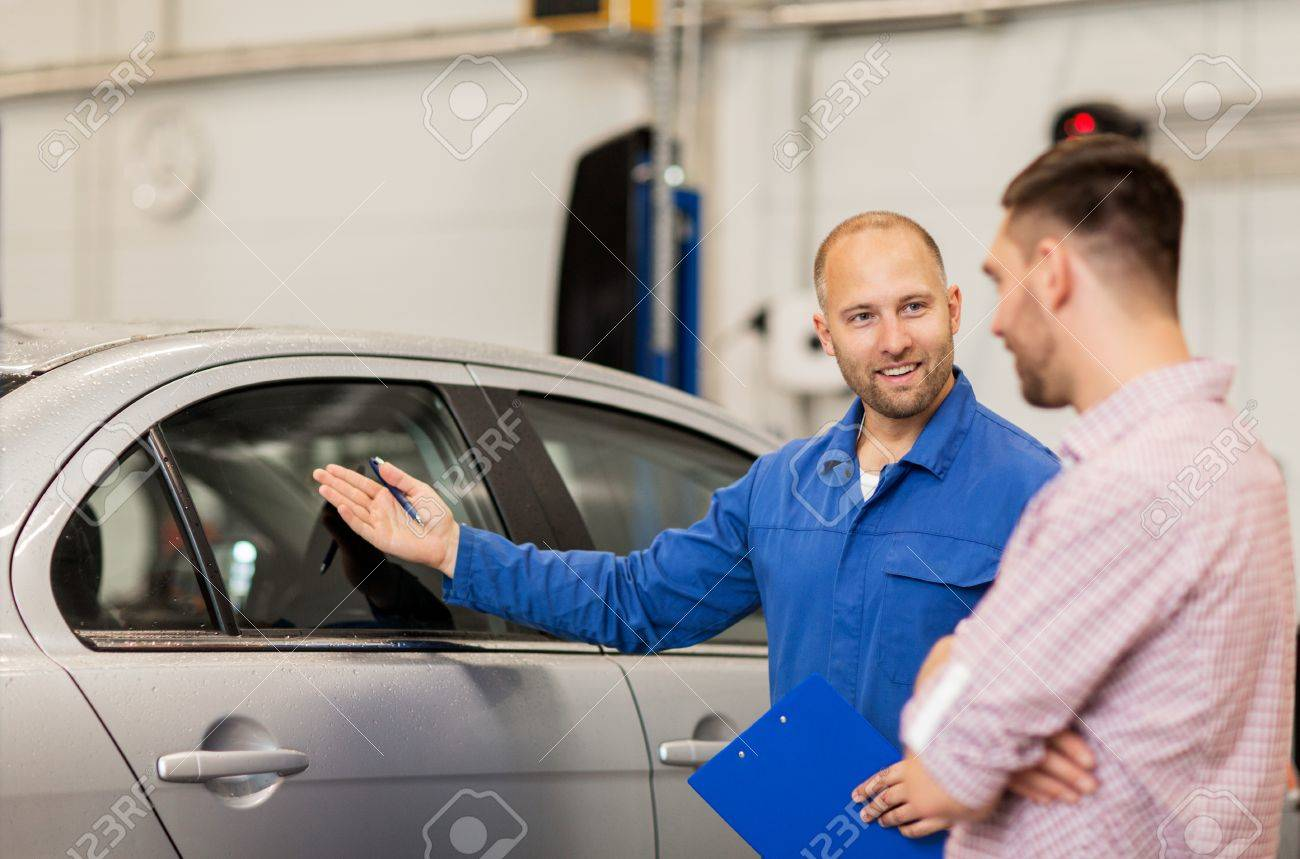 auto service, repair, maintenance and people concept - mechanic with clipboard showing side window to man or owner at car shop Standard-Bild - 64861704