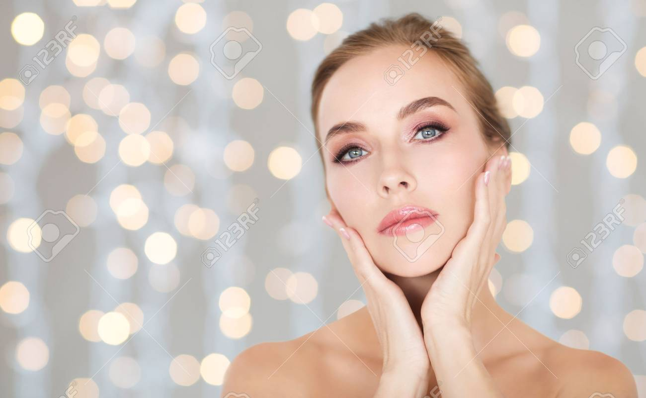 beauty, people and health concept - beautiful young woman touching her face over holidays lights background Standard-Bild - 67176390