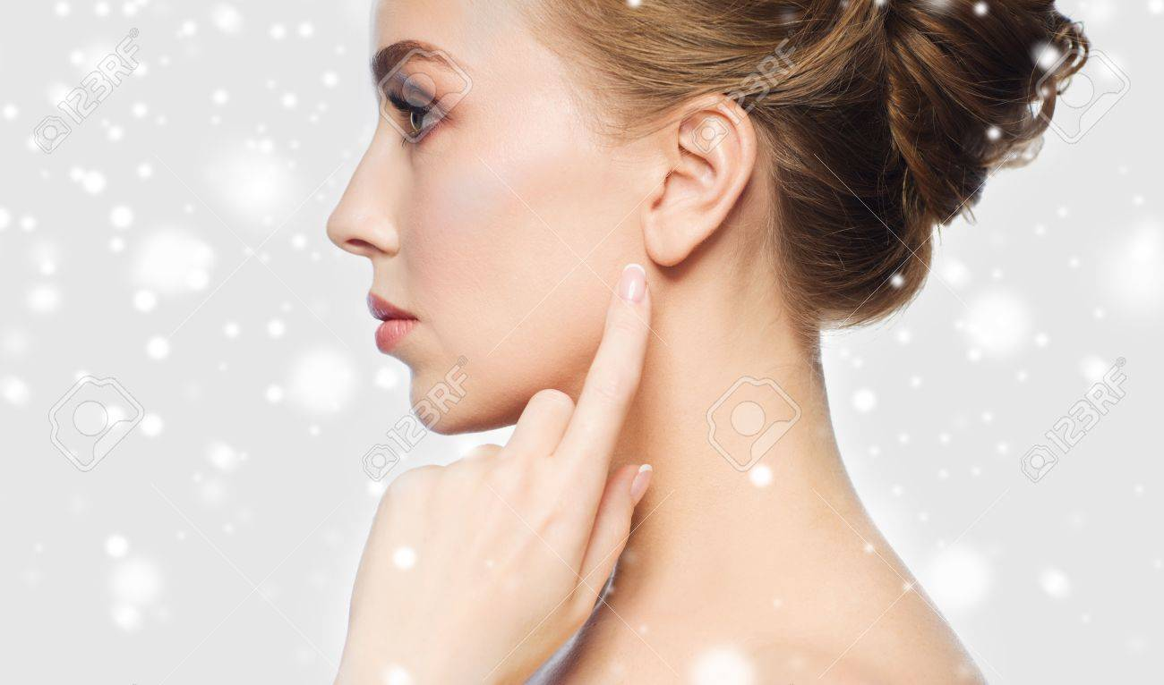 health, people, winter and beauty concept - close up of beautiful young woman pointing finger to her ear over gray background and snow Standard-Bild - 65203452