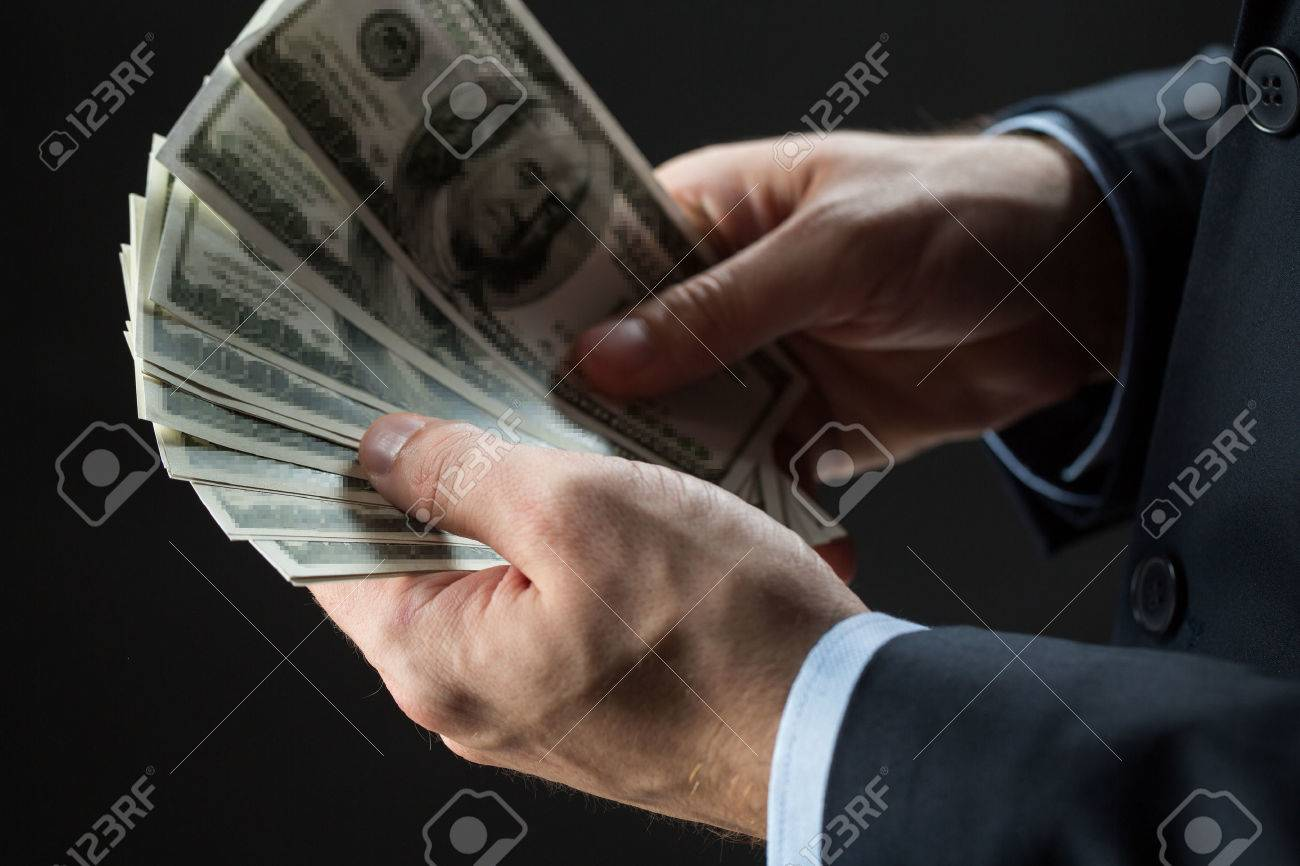 people, business, finances and money concept - close up of businessman hands holding dollar cash over black background Standard-Bild - 65206035
