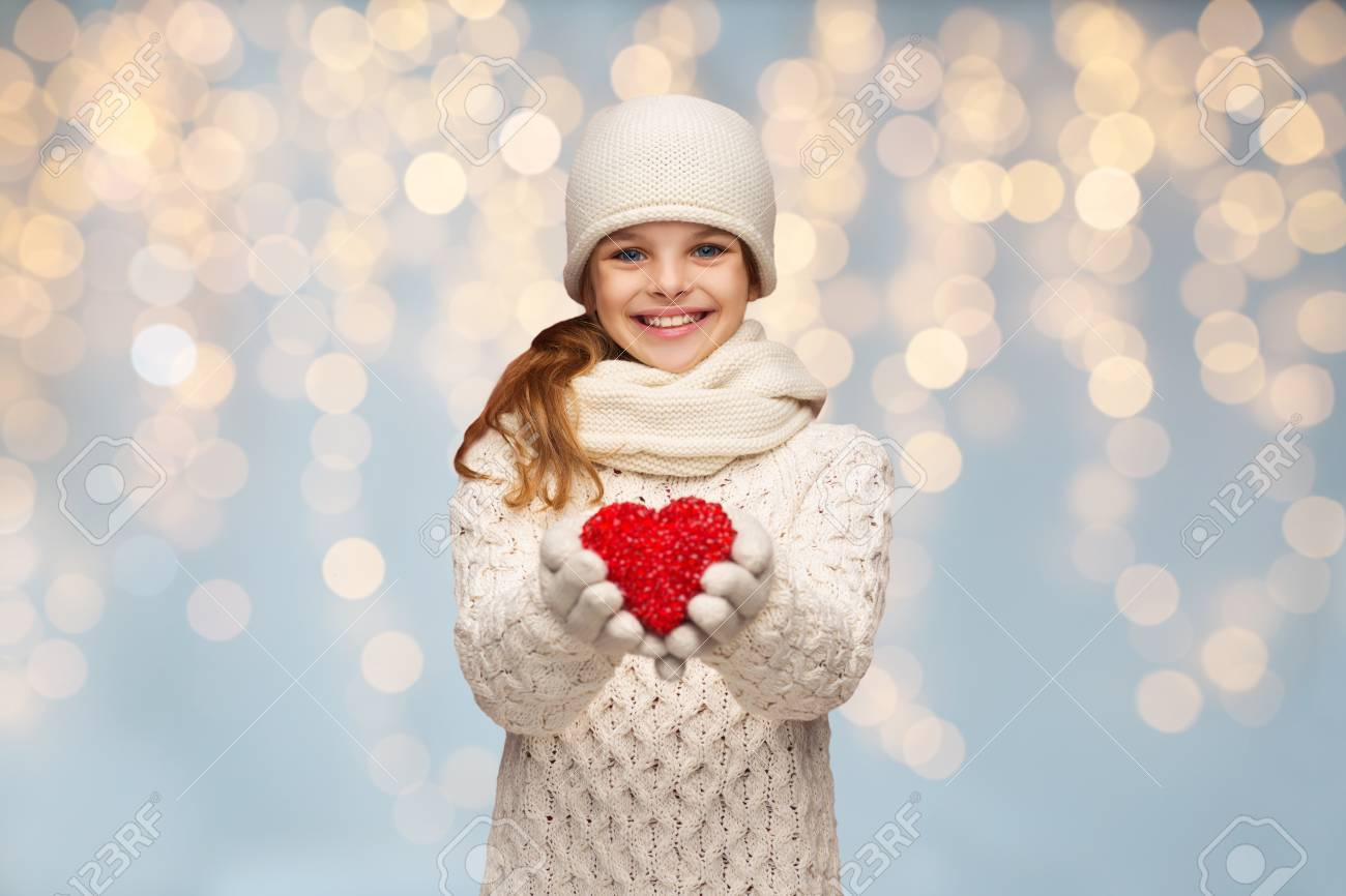 people, christmas, holidays, charity and love concept - smiling teenage girl in winter clothes with small red heart over lights background Standard-Bild - 65207302