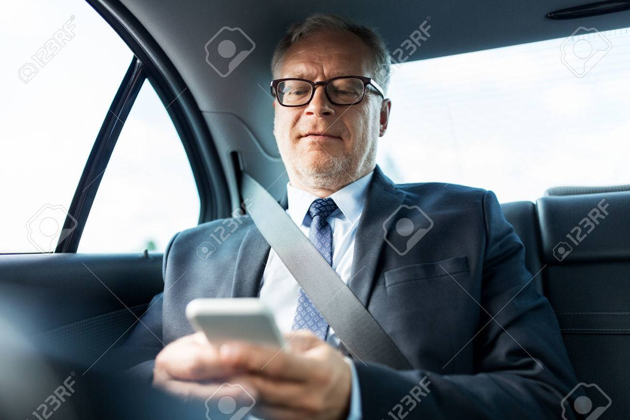 transport, business trip, technology and people concept - senior businessman texting on smartphone and driving on car back seat Standard-Bild - 65346011
