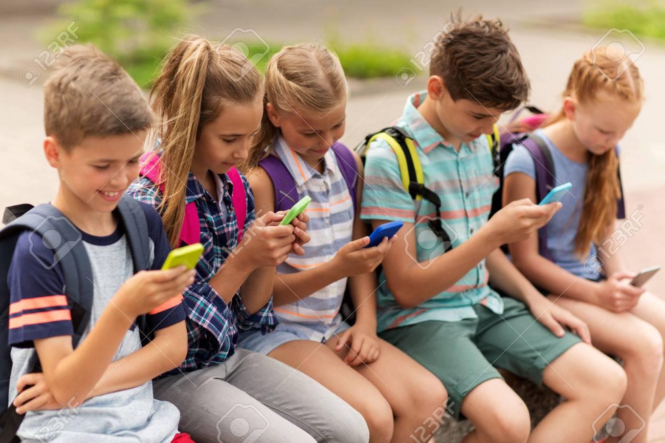 Grundschulbildung, Freundschaft, Kindheit, Technologie und Menschen Konzept - Gruppe von glücklichen Grundschüler mit Smartphones und Rucksäcken auf der Bank sitzen im Freien Standard-Bild - 65551235