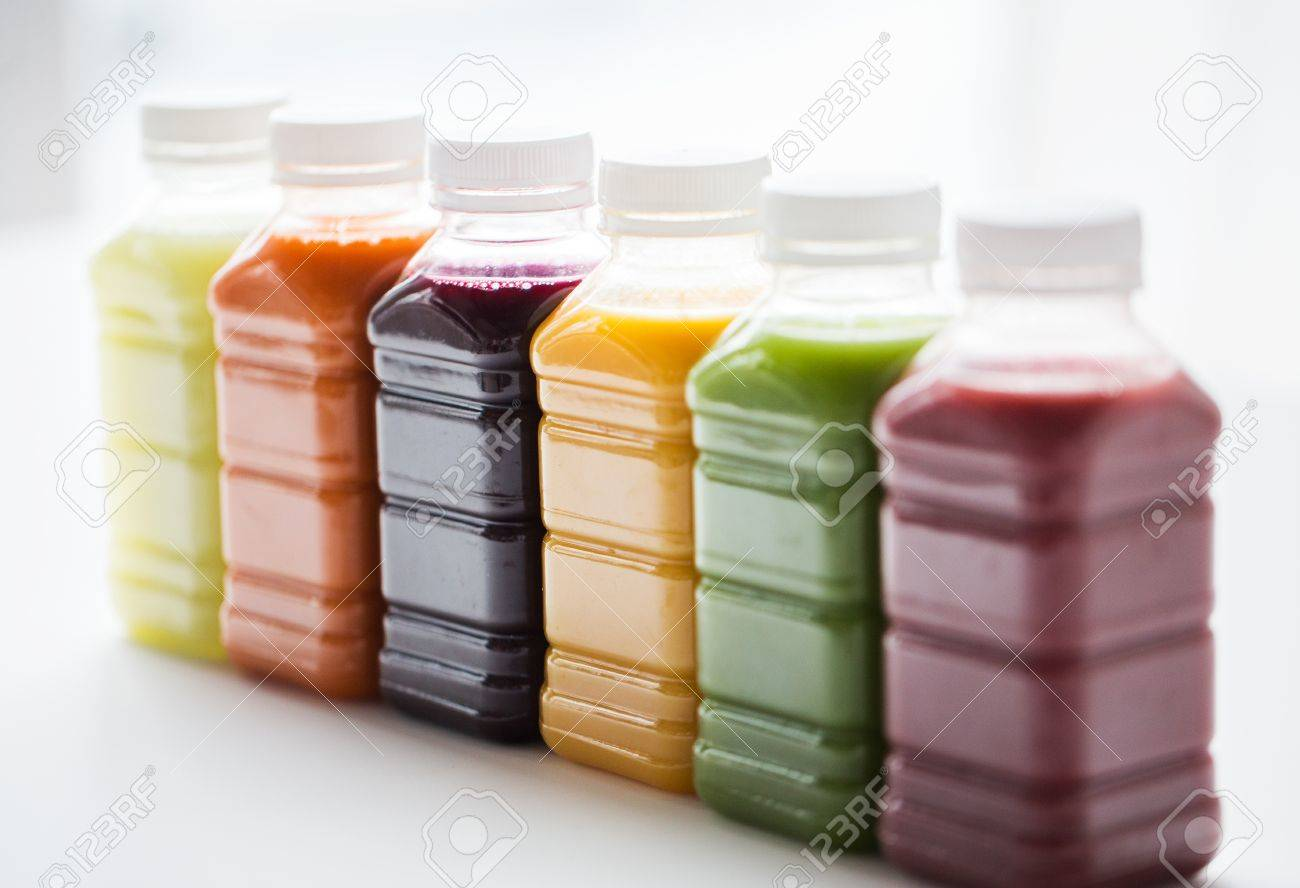 healthy eating, drinks, diet and detox concept - close up of plastic bottles with different fruit or vegetable juices on white Standard-Bild - 65552867