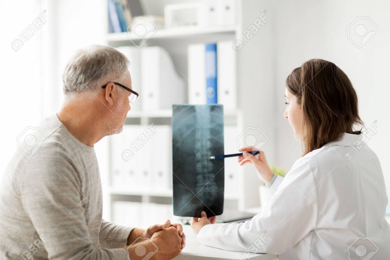 medicine, healthcare, surgery, radiology and people concept - doctor showing x-ray of spine to senior man at hospital Standard-Bild - 65746591