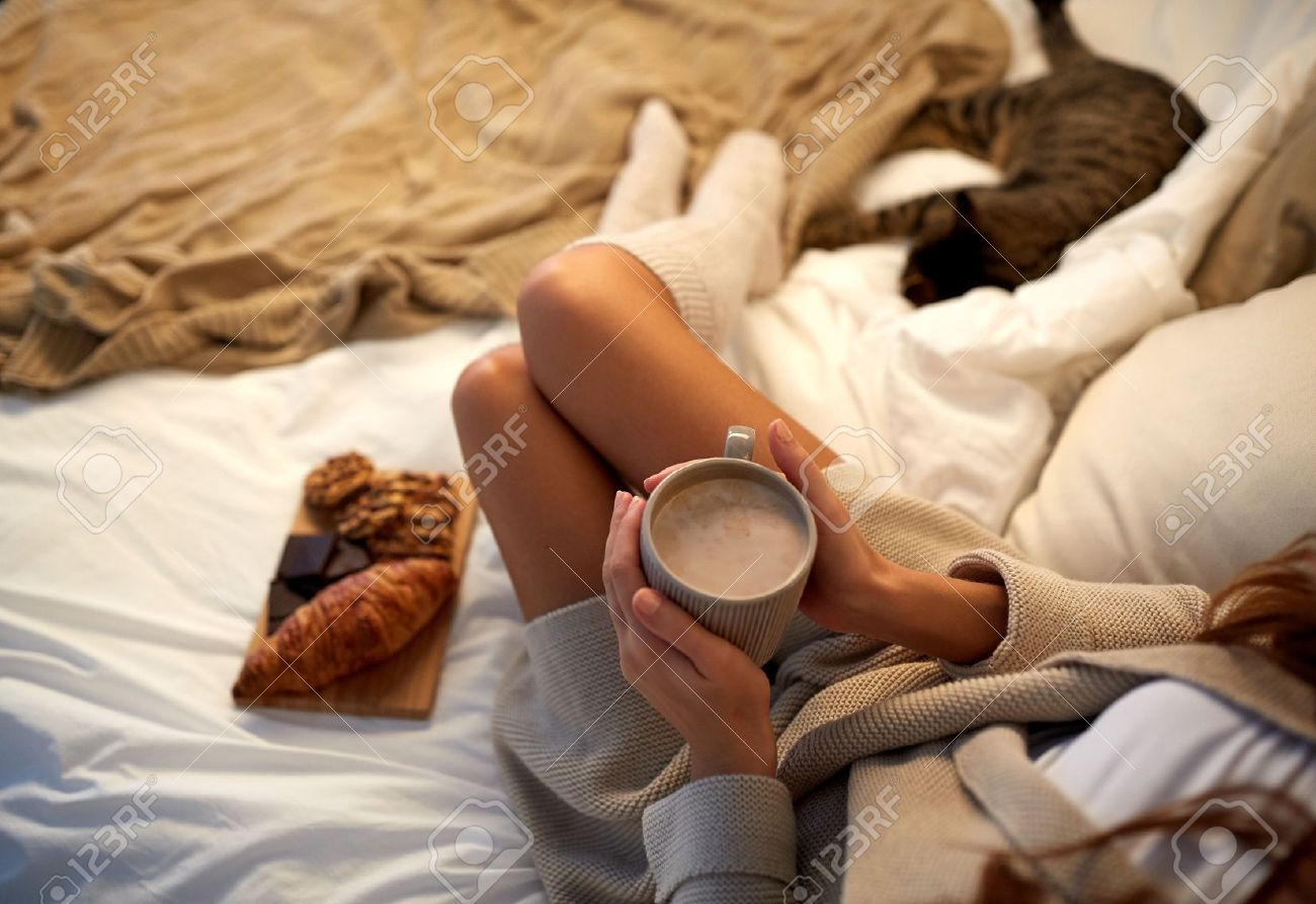 winter, coziness, leisure and people concept - close up of young woman with cup of coffee or cacao and sweets in bed at home Standard-Bild - 66157400