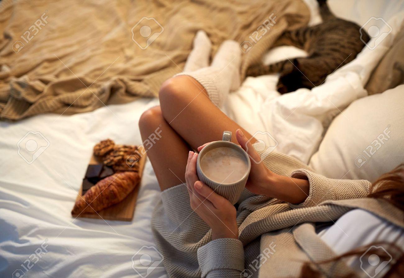 Winter, Gemütlichkeit, Freizeit und Menschen Konzept - Nahaufnahme zu Hause der jungen Frau mit einer Tasse Kaffee oder Kakao und Süßigkeiten im Bett Standard-Bild - 66157400