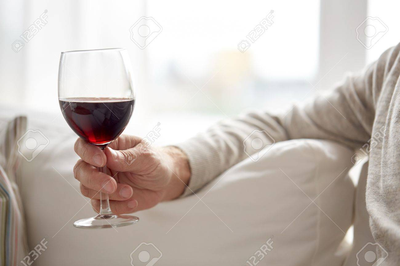 people, alcohol and drinks concept - close up of senior man hand holding glass with red wine at home Standard-Bild - 66971943