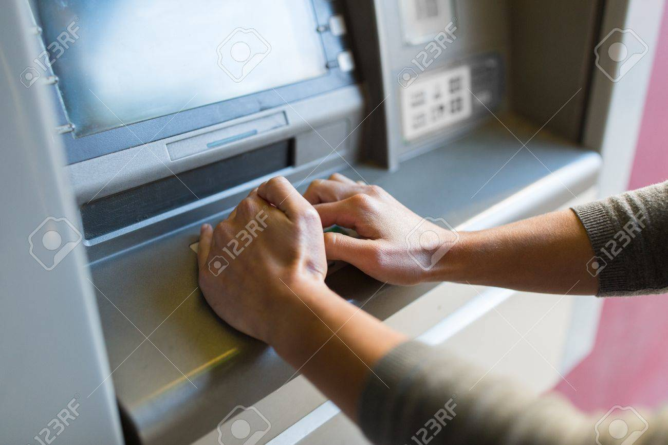 finance, money, bank and people concept - close up of hand entering pin code at atm machine Standard-Bild - 67412202