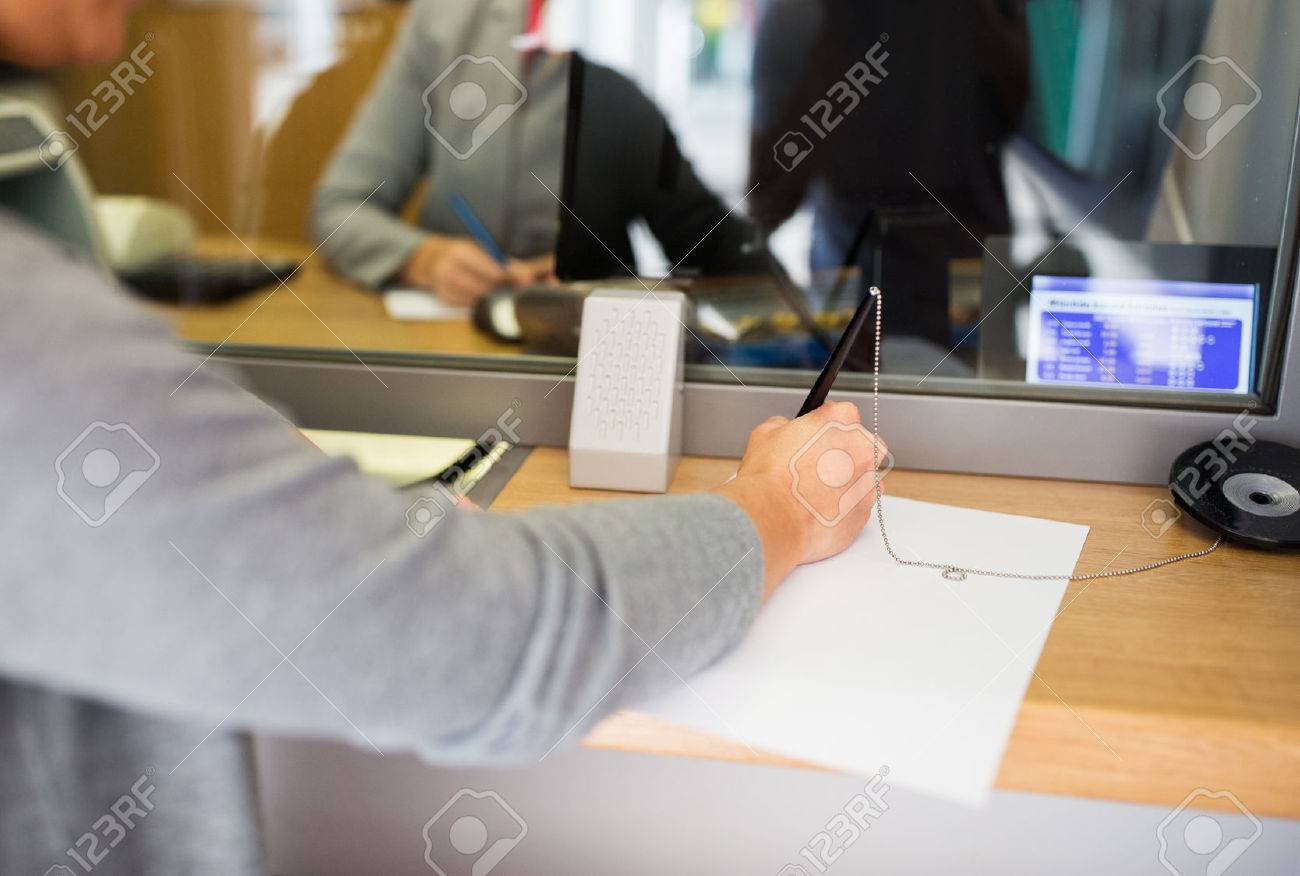 people and finance concept - customer with pen and paper writing application at bank office Standard-Bild - 67412260