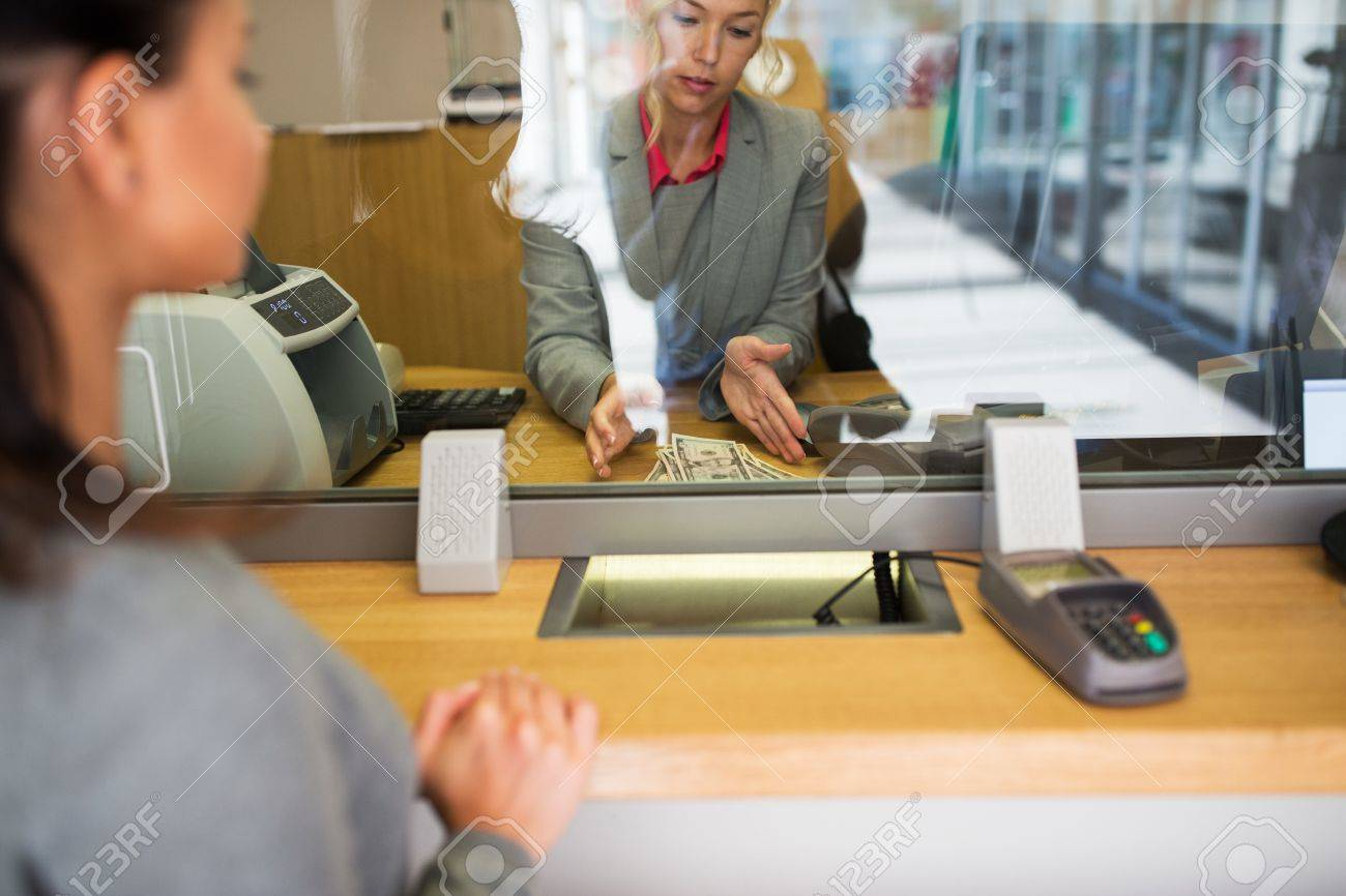 clerk with cash money and customer at bank office Standard-Bild - 68492877