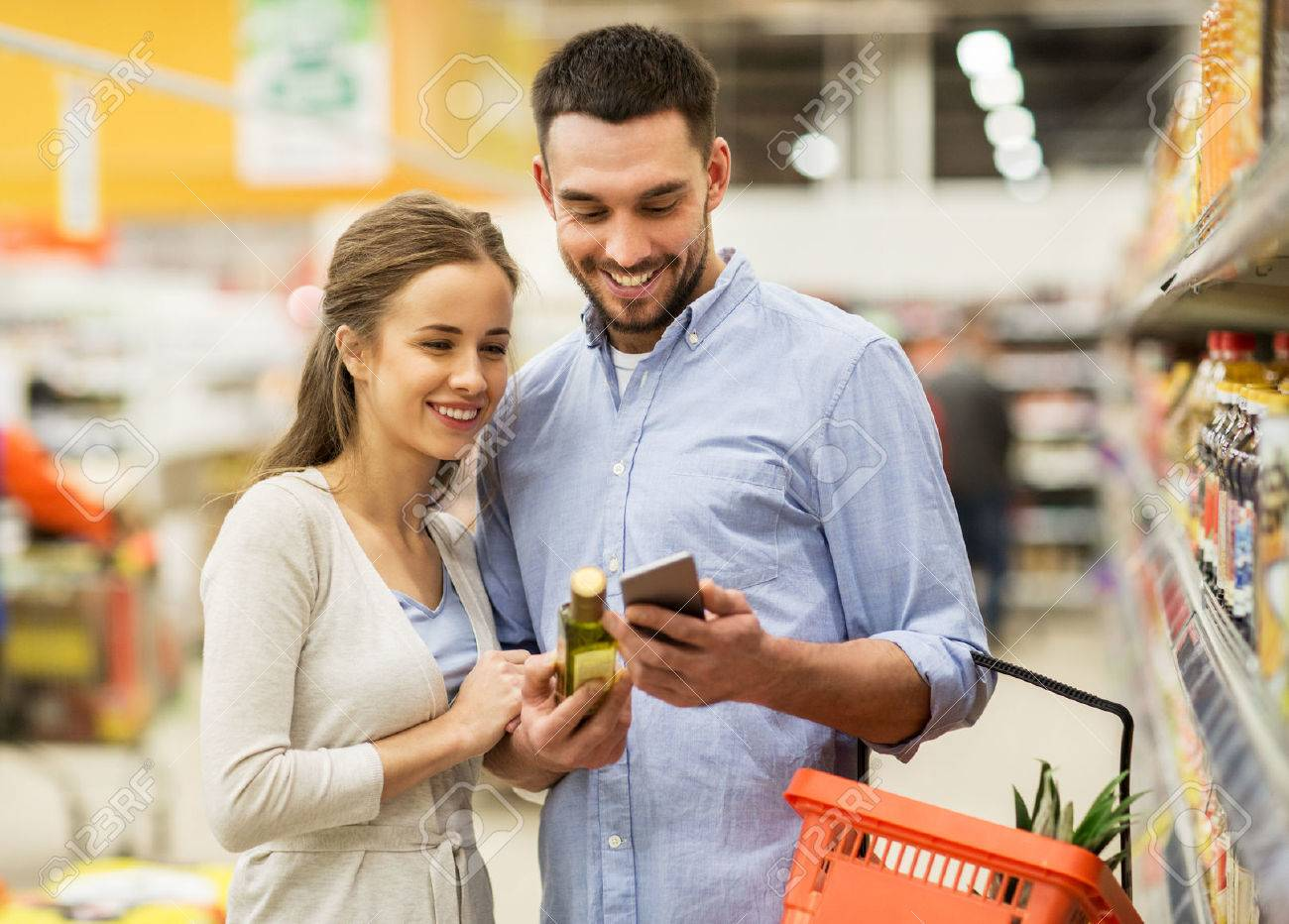 couple with smartphone buying olive oil at grocery Standard-Bild - 69511807