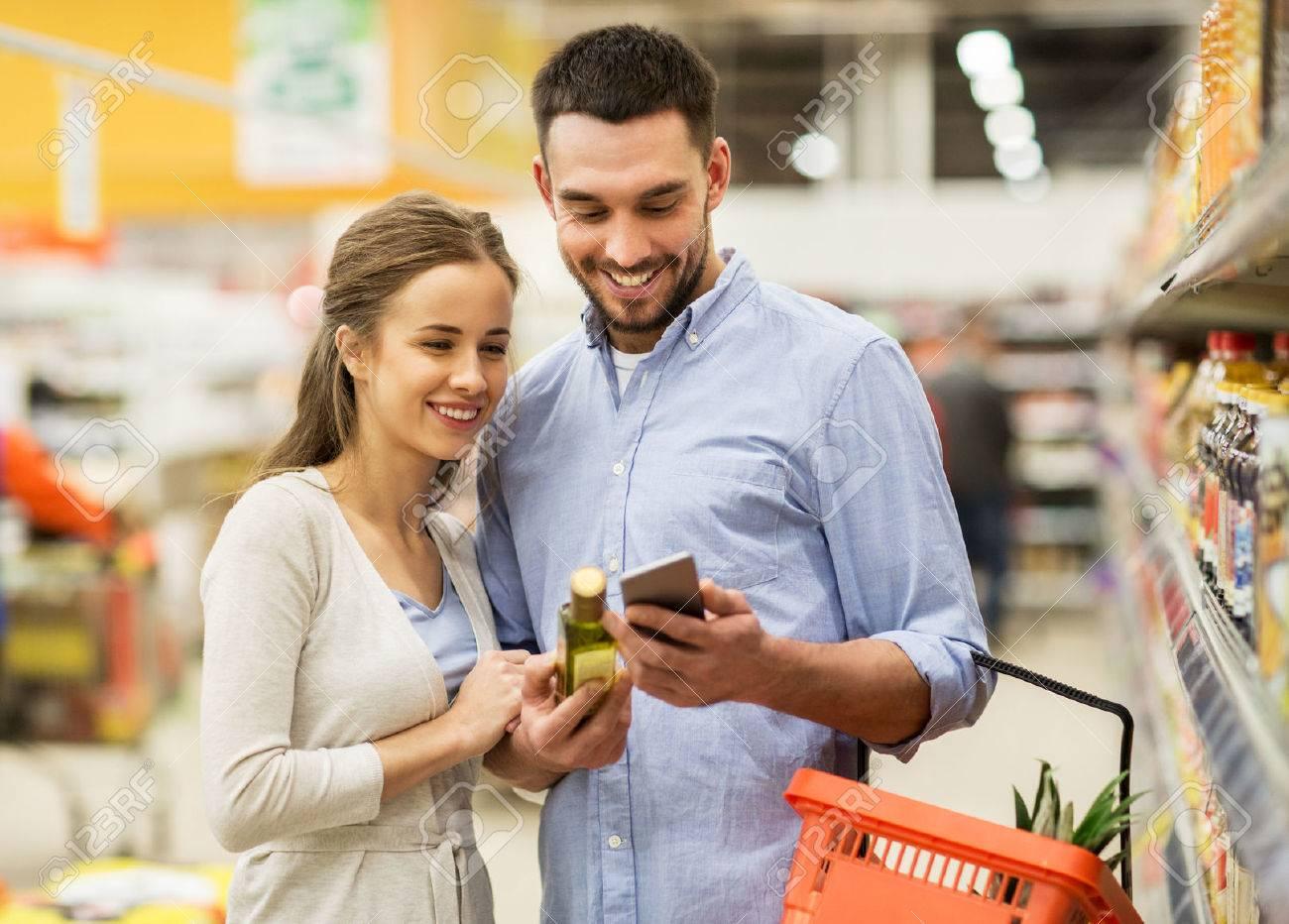 Paar mit Smartphone Olivenöl auf Lebensmittelgeschäft zu kaufen Standard-Bild - 69511807