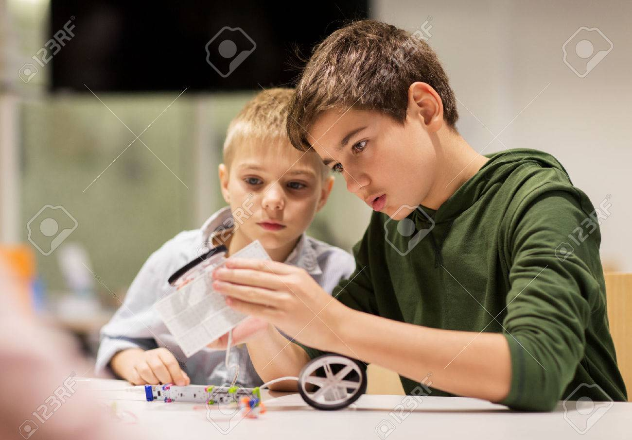 education, children, technology, science and people concept - happy boys building robots at robotics school lesson Standard-Bild - 69836594