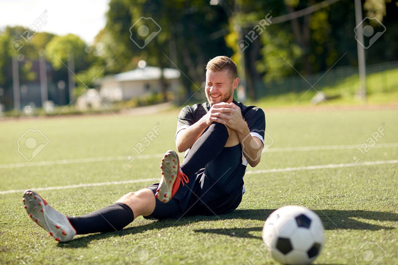 injured soccer player with ball on football field Standard-Bild - 71148982