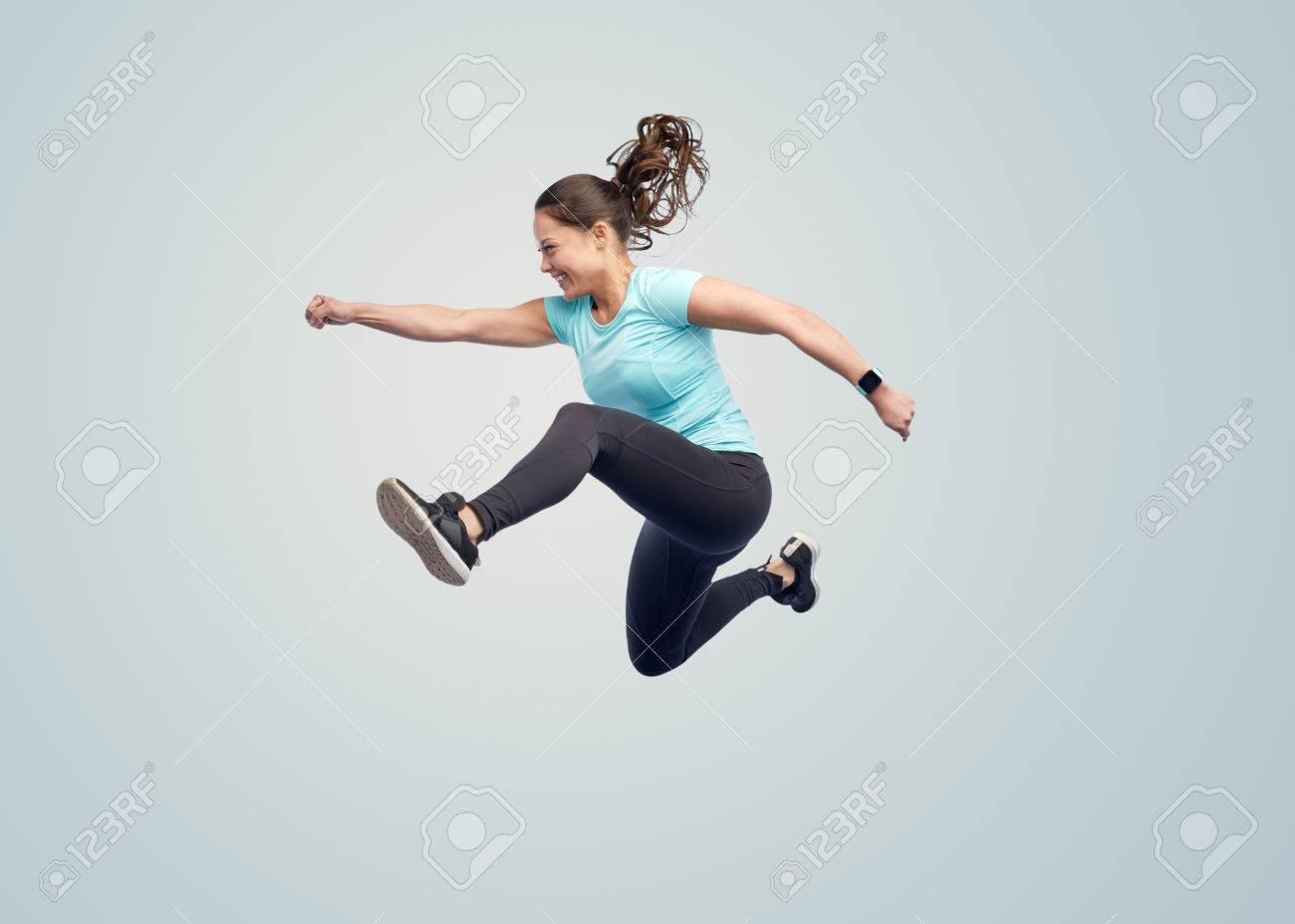 Sport, Fitness, Bewegung und Menschen Konzept - glückliche junge Frau lächelnd in Luft über blauen Hintergrund springen Standard-Bild - 72277645