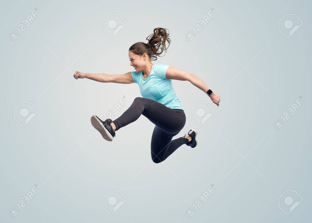 sport, fitness, motion and people concept - happy smiling young woman jumping in air over blue background Standard-Bild - 72277645