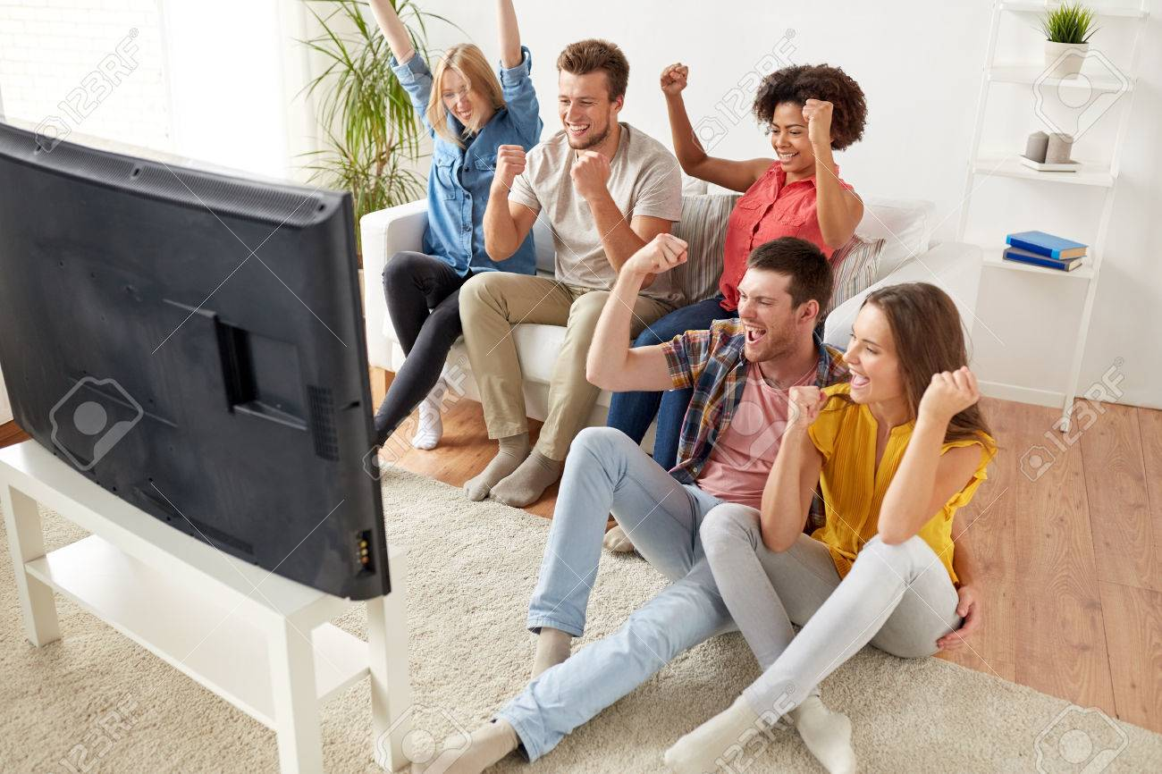 happy friends with remote watching tv at home Standard-Bild - 73727108