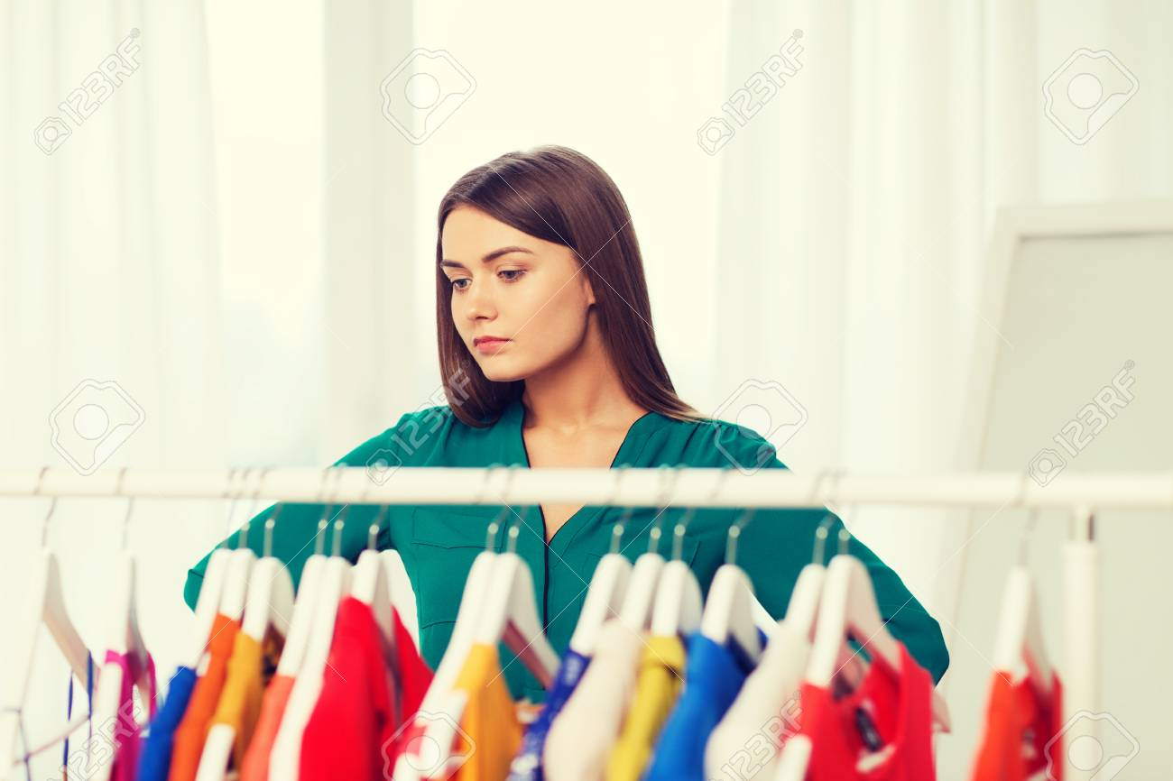 e24b7c23 nothing to wear, clothing, fashion and style concept - woman choosing  clothes at home