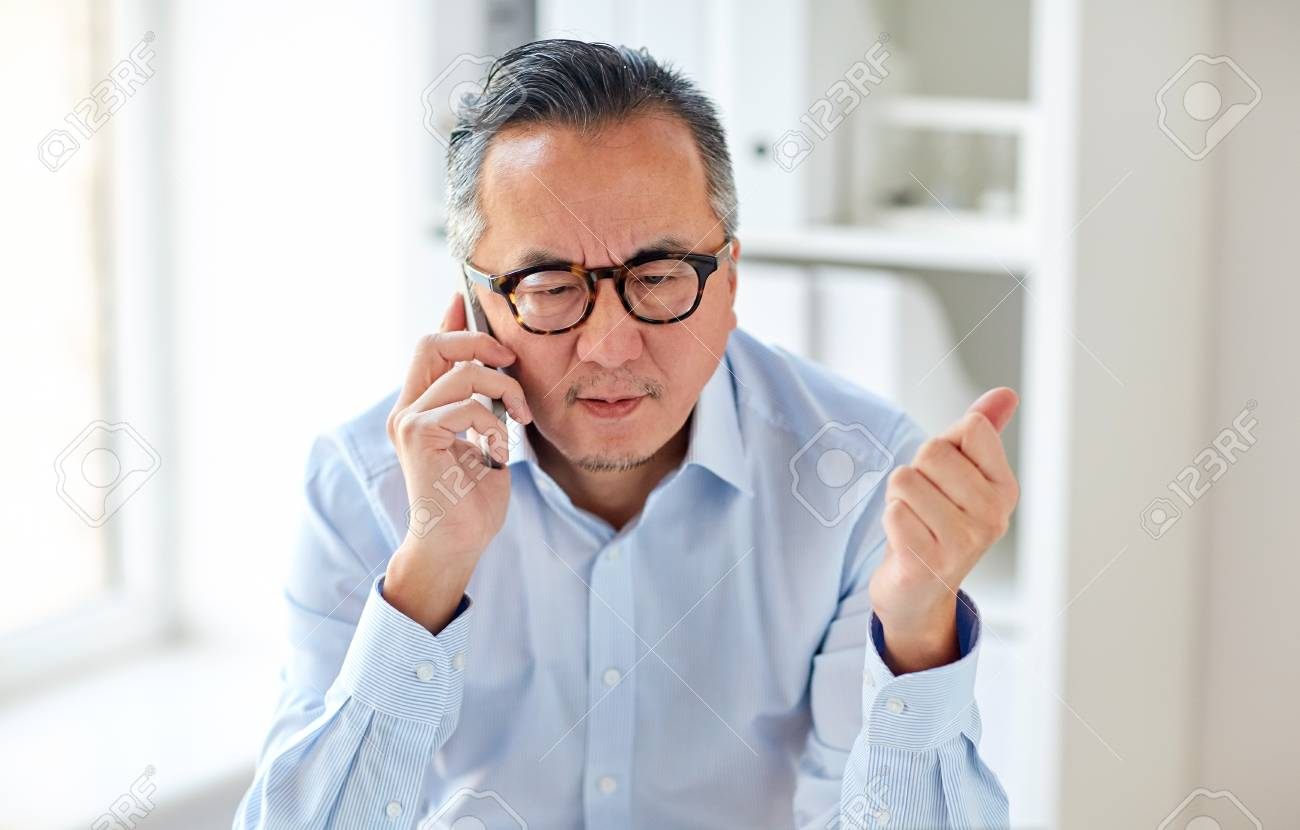 business, people, communication and technology concept - serious asian businessman calling on smartphone in office - 76882500