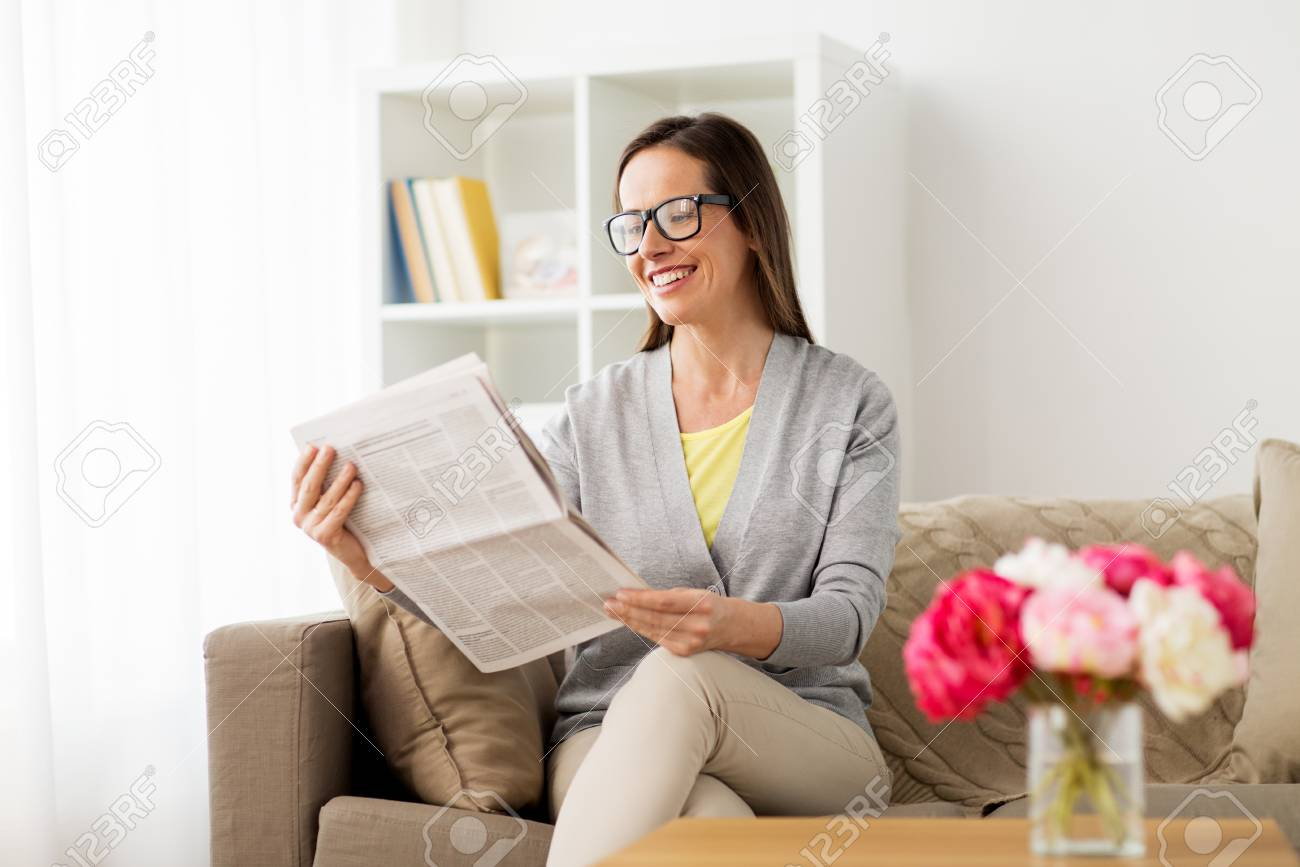 mass media and people concept - happy woman reading newspaper
